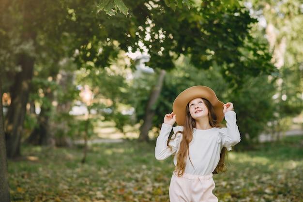 Menina em um parque em pé em um parque com um chapéu marrom