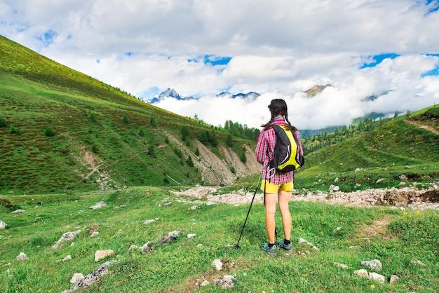 Menina em um prado na montanha durante uma caminhada