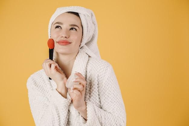 Menina em um roupão de banho. maquia-se