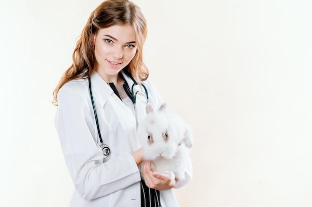 Menina em um terno de um médico veterinário com um coelho nas mãos