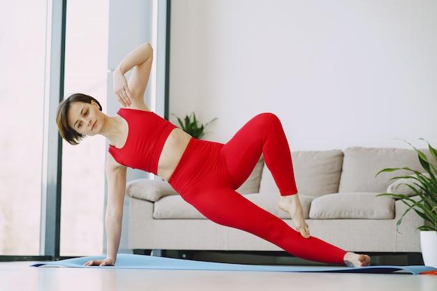 Menina em um uniforme vermelho esportes praticando ioga em casa