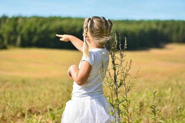 Menina em um vestido branco em um campo mostra o dedo na floresta em uma tarde ensolarada
