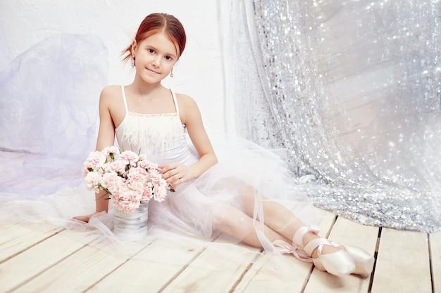 Menina em um vestido de baile branco e sapatos, lindo cabelo vermelho. jovem atriz de teatro. pequeno balé prima. jovem bailarina se preparando para uma apresentação de balé