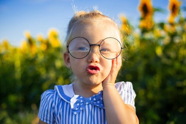 Menina em um vestido e óculos no fundo de um campo de girassol. rosto emocional.