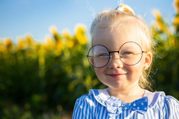 Menina em um vestido e óculos no fundo de um campo de girassol.
