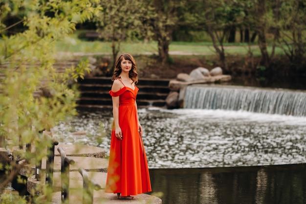 Menina em um vestido longo vermelho perto do lago do parque ao pôr do sol.
