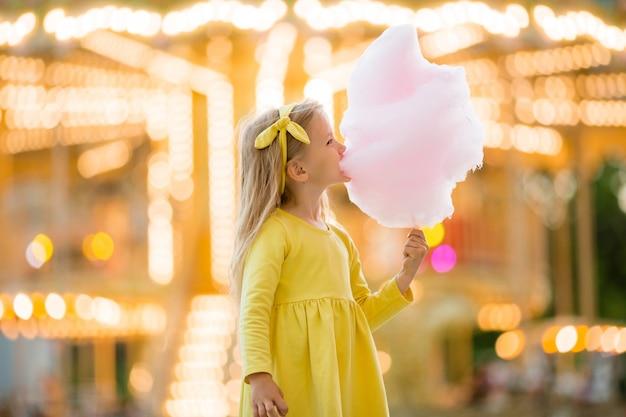 Menina em uma caminhada em um parque de diversões comendo algodão doce