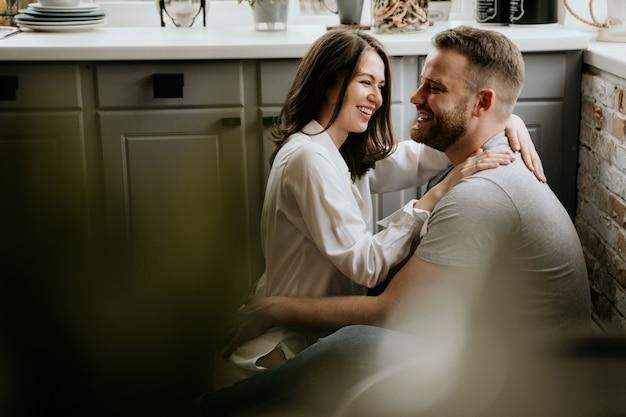 Menina em uma camisa branca e um cara em uma t-shirt cinza na cozinha. beijar e abraçar.