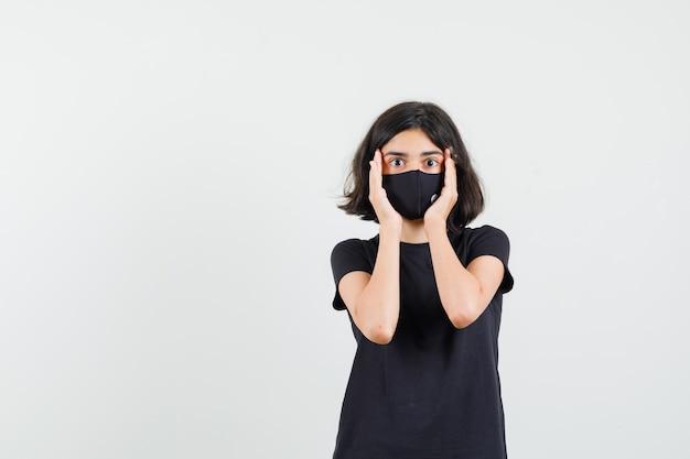 Menina em uma camiseta preta, máscara de mãos dadas no rosto e olhando surpresa, vista frontal.