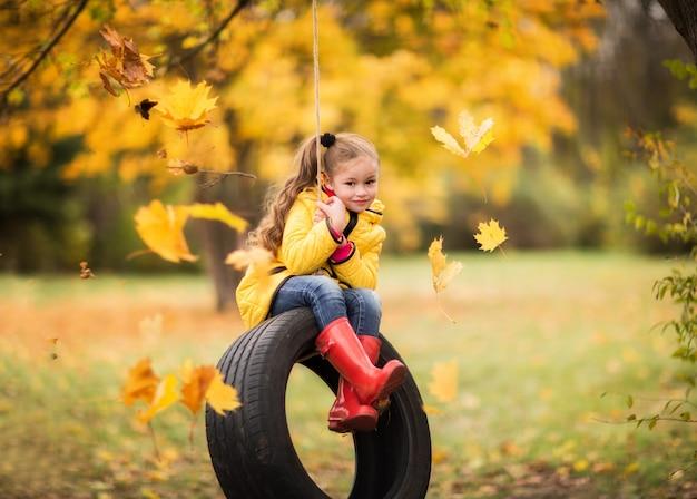 Menina em uma capa de chuva amarela monta um pneu no parque outono