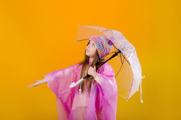 Menina em uma capa de chuva rosa e um chapéu de malha está segurando um guarda-chuva em um espaço amarelo