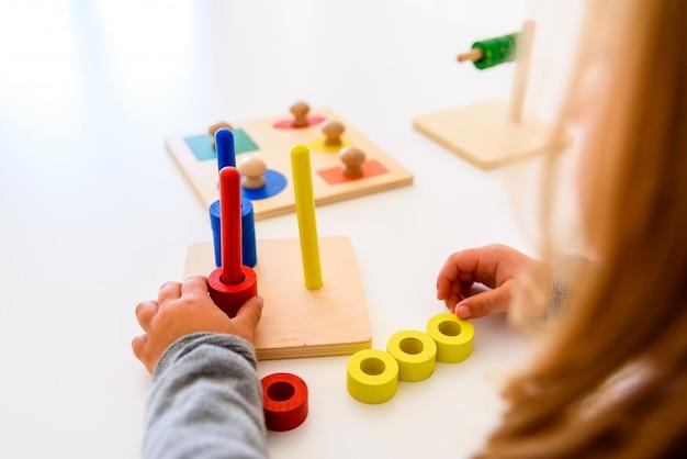 Menina em uma escola que desenvolve suas habilidades motoras nas mãos usando um material de madeira colorido.