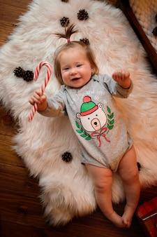 Menina em uma fantasia de natal vermelha com guirlandas retrô senta-se em uma pele