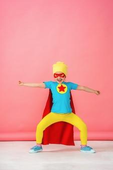 Menina em uma fantasia de super-herói em capa vermelha e chapéu mostra como ela é forte.