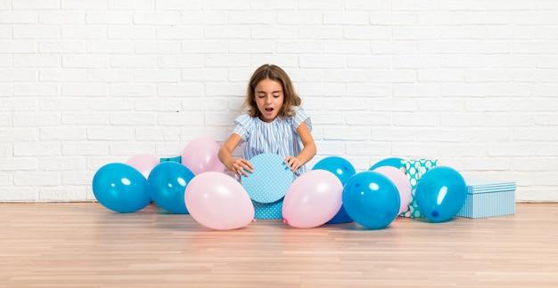 Menina em uma festa de aniversário, abrindo um presente com gesto de surpresa