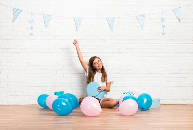 Menina em uma festa de aniversário, abrindo um presente