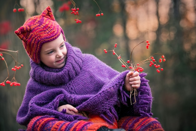 Menina em uma floresta de outono sentada em um toco de árvore coberto de musgo em um terno de malha e um chapéu com orelhas de chanterelle e olha para bagas vermelhas em um galho