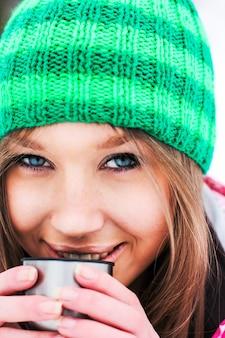 Menina em uma jaqueta carmesim e chapéu verde bebendo chá quente de um termo em montanhas nevadas