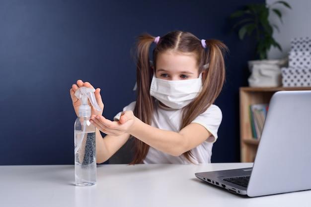 Menina em uma máscara médica estuda em um laptop em casa, desinfecção das mãos. conceito de quarentena do vírus corona covid-19.