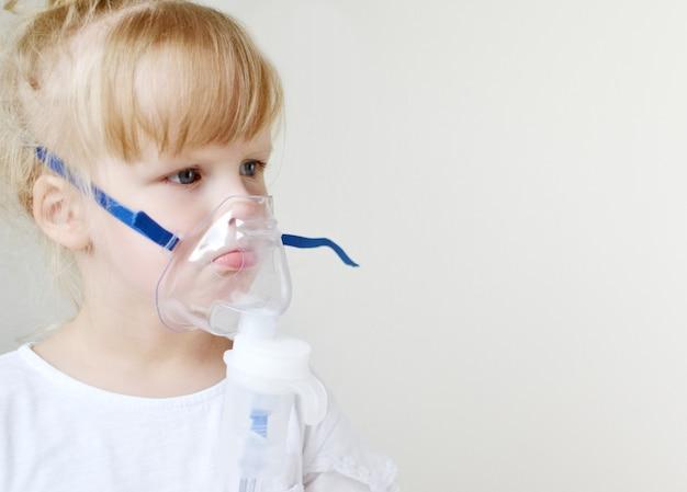 Menina em uma máscara para inalações, fazendo inalação com nebulizador em casa inalador na mesa, interior, criança doente