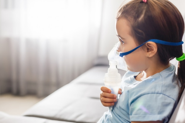 Menina em uma máscara, trato respiratório de tratamentos com um nebulizador em casa