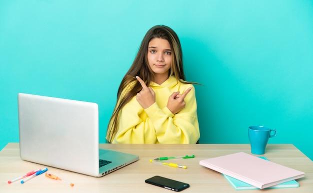 Menina em uma mesa com um laptop sobre fundo azul isolado apontando para as laterais tendo dúvidas