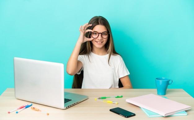 Menina em uma mesa com um laptop sobre fundo azul isolado, mostrando sinal de ok com os dedos