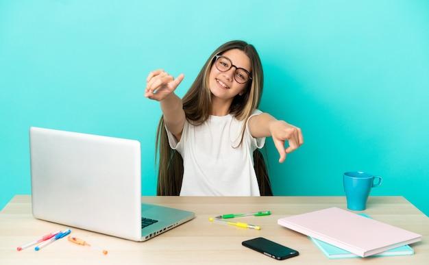 Menina em uma mesa com um laptop sobre um fundo azul isolado apontando para a frente com uma expressão feliz
