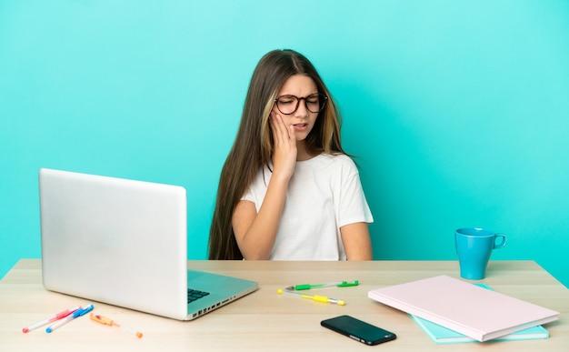 Menina em uma mesa com um laptop sobre um fundo azul isolado com dor de dente