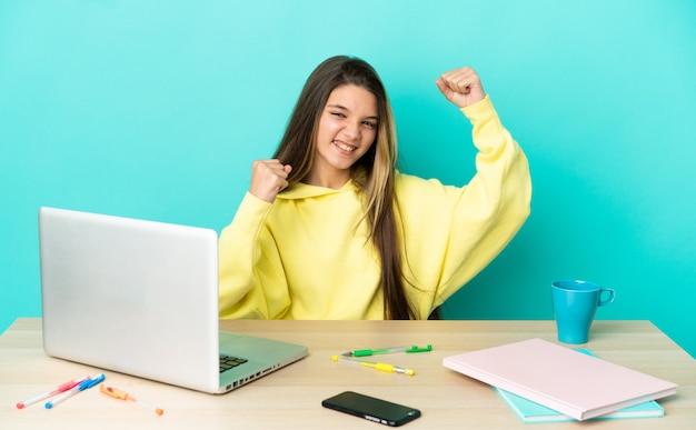 Menina em uma mesa com um laptop sobre um fundo azul isolado, comemorando uma vitória