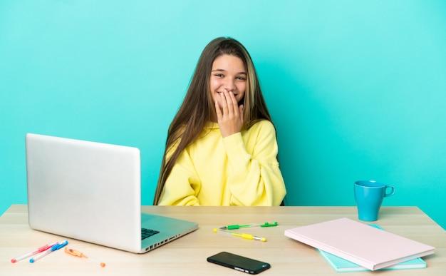 Menina em uma mesa com um laptop sobre um fundo azul isolado feliz e sorridente, cobrindo a boca com a mão