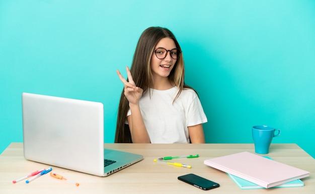 Menina em uma mesa com um laptop sobre um fundo azul isolado, sorrindo e mostrando o sinal da vitória