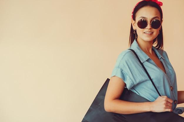 Menina em uma parede amarela com sacolas de compras