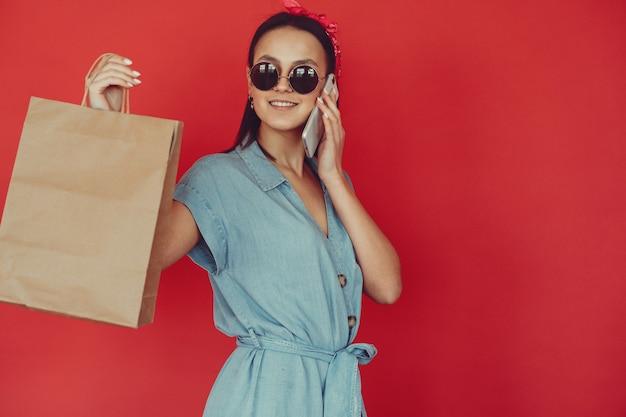 Menina em uma parede vermelha com sacolas de compras