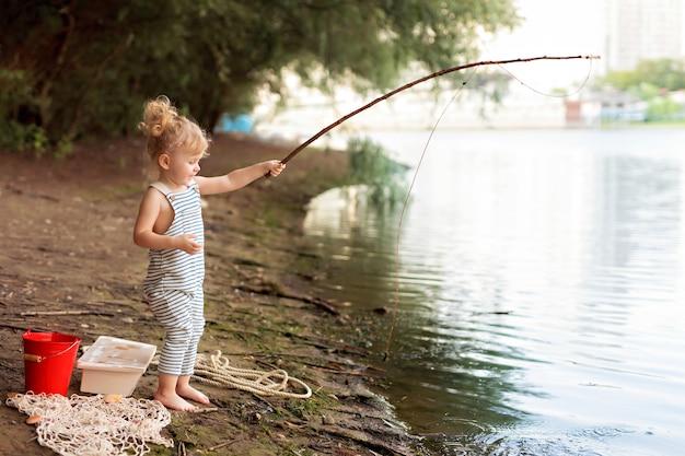 Menina em uma praia de areia com uma vara de pescar