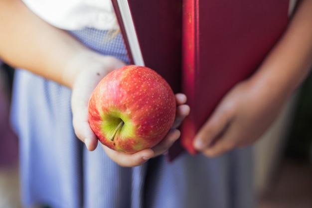 Menina, em, uniforme, com, maçã, e, livros, em, mãos