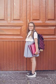 Menina, em, uniforme escola, com, mochila, antes de, grande, portas