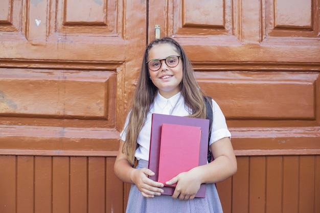 Menina, em, uniforme escola, em, óculos, segurando, livros, e, sorrindo