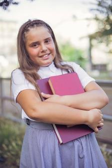 Menina, em, uniforme escola, ficar, e, segurando livros, em, braços
