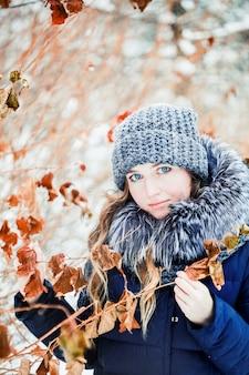 Menina em winter park coberto de neve com folhas secas