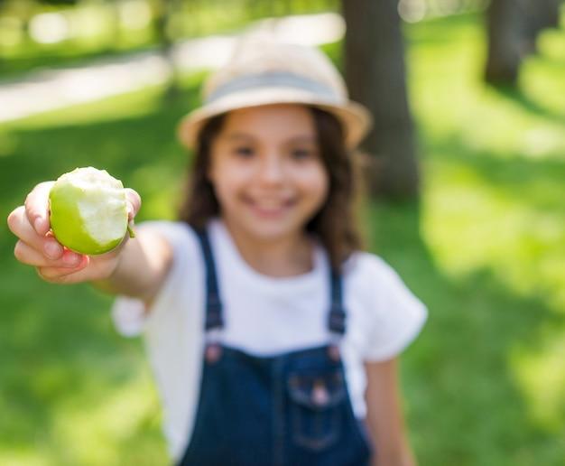Menina embaçada segurando uma maçã verde