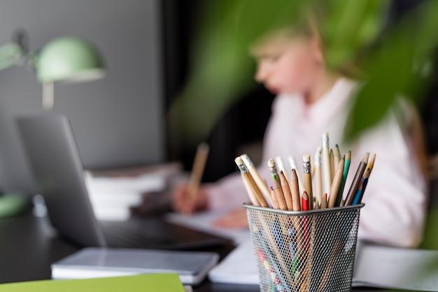 Menina embaçada tomando notas na aula on-line
