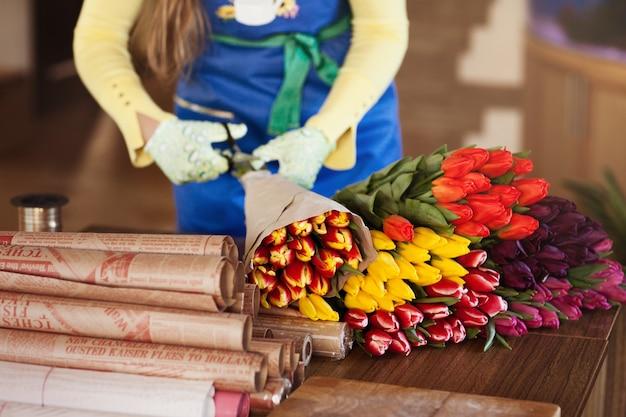 Menina embala buquês coloridos de tulipas em papel ofício