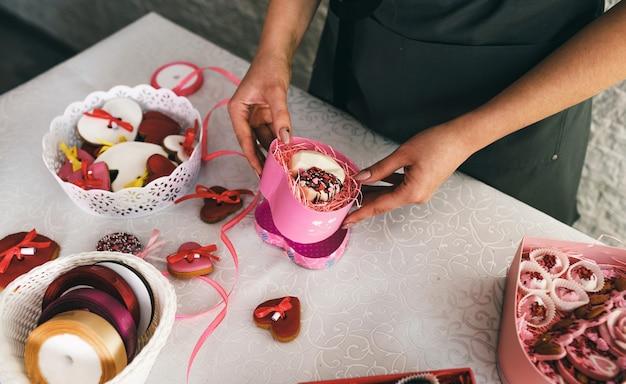Menina embala em uma caixa de presente bolos em forma de um coração.