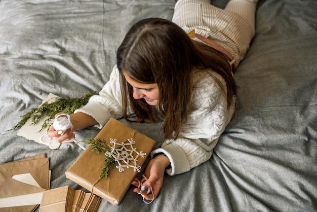 Menina embrulhando presentes com decoração de natal