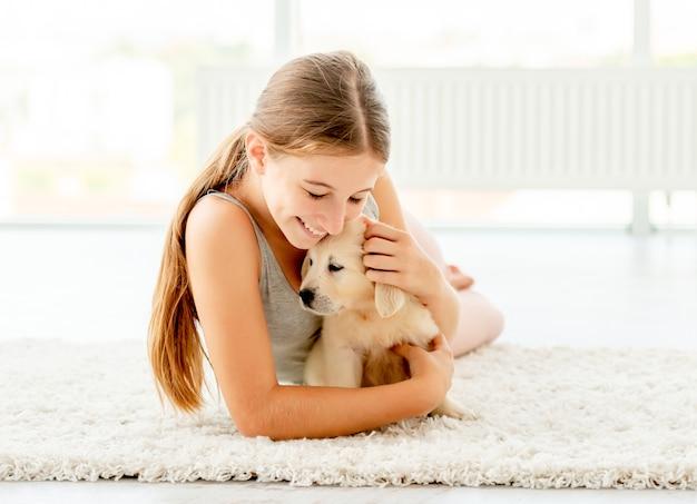 Menina emocional, abraçando o filhote de retriever
