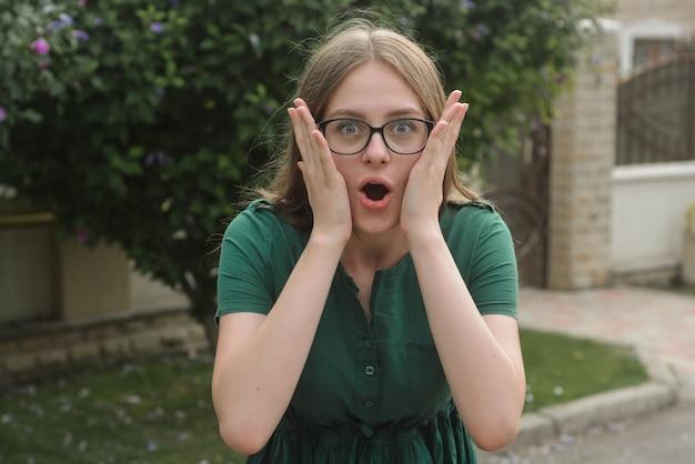 Menina emocional adolescente surpirized, em vestido verde