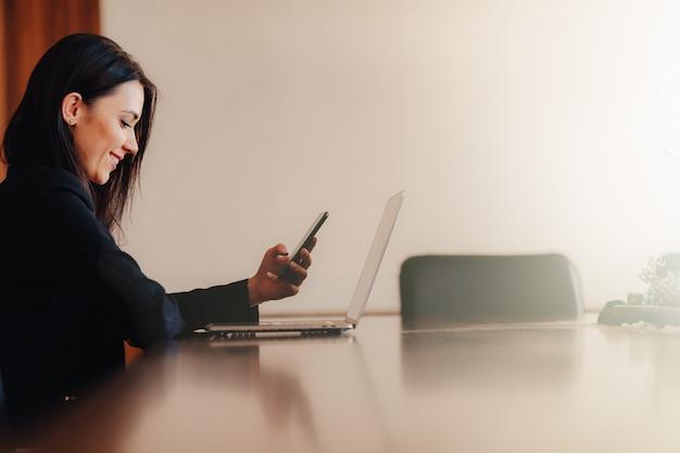 Menina emocional atrativa nova na roupa do estilo do negócio que senta-se na mesa com o telefone no escritório ou na audiência