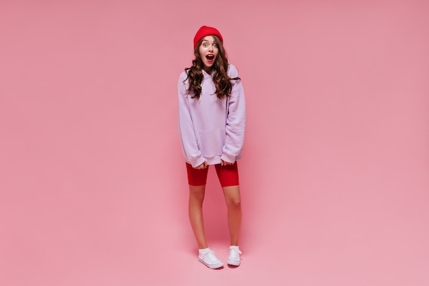 Menina emocional chocada em shorts vermelhos e moletom roxo olhando para a câmera