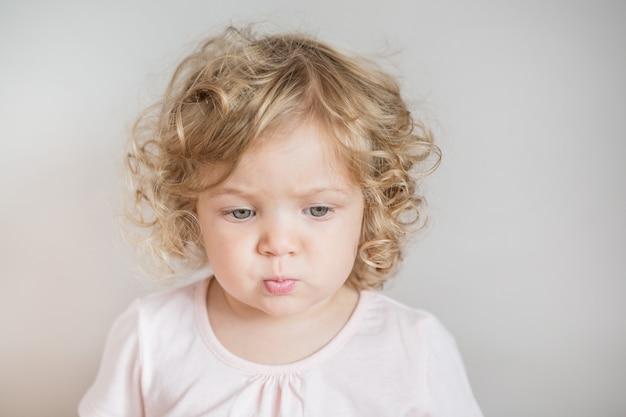 Menina emocional encaracolada olhando para uma parede cinza claro